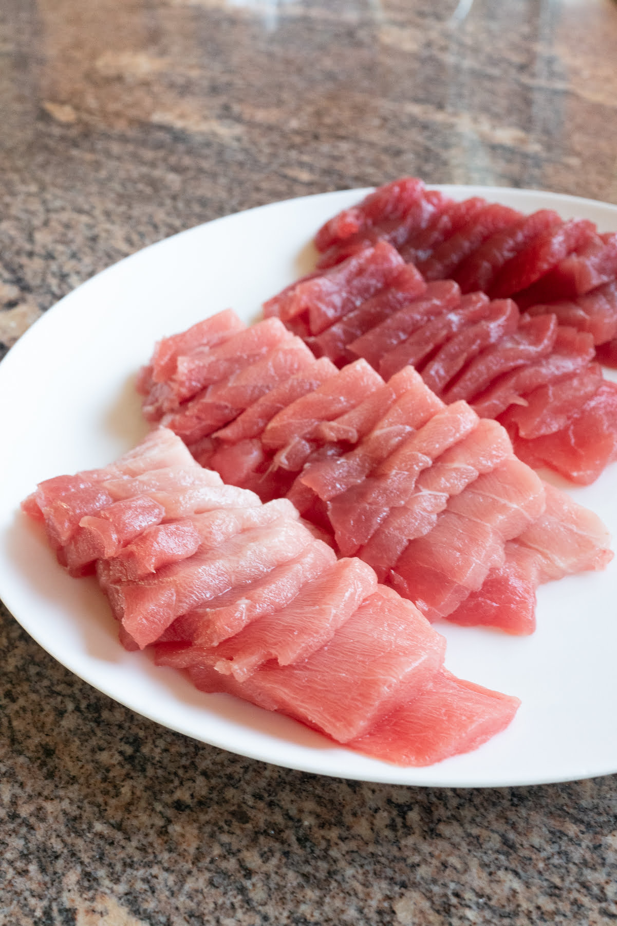 A plate of fresh ahi sashimi, sliced and ready to use for homemade sushi.
