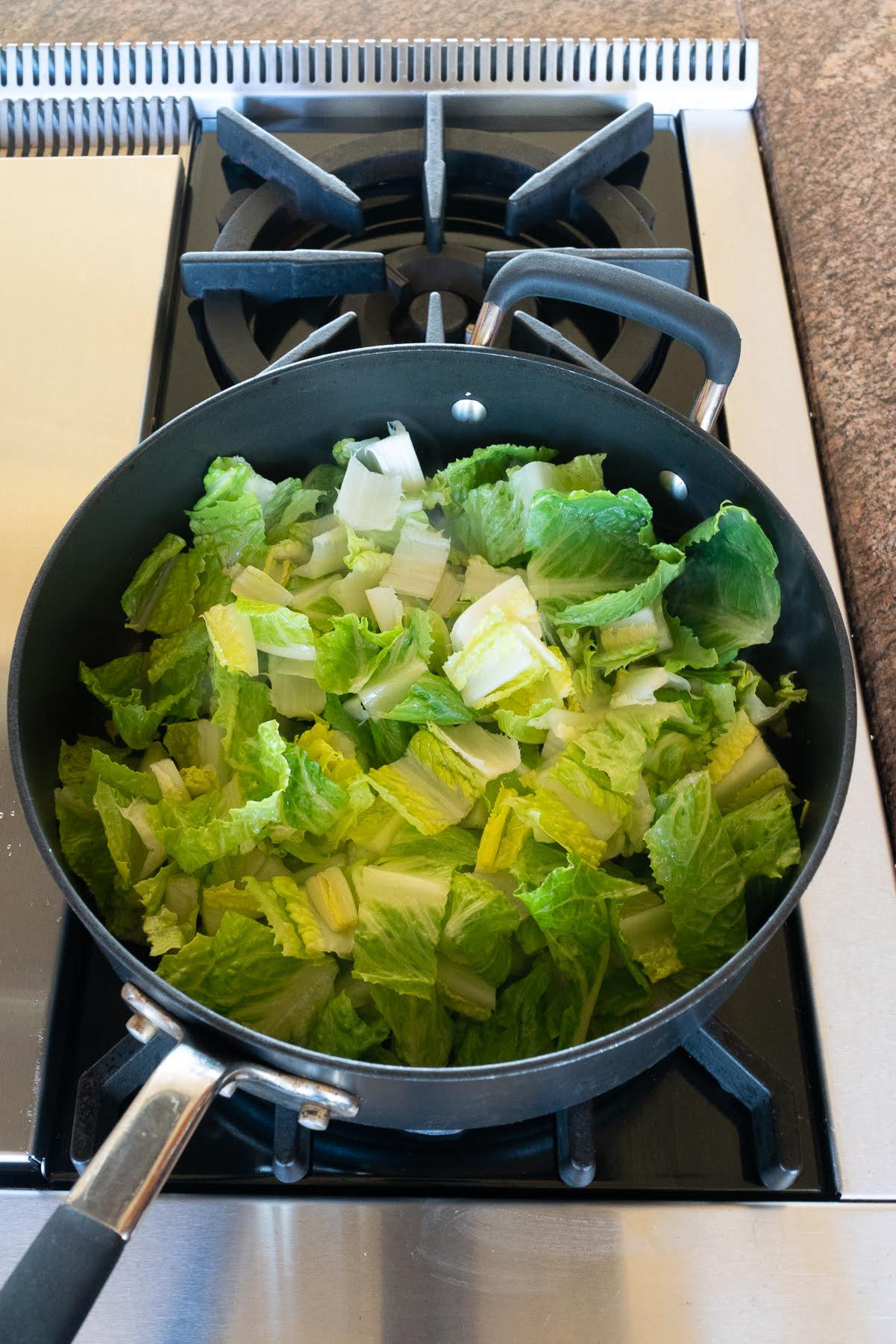 Sautéing lettuce in a pan.