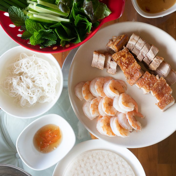Laying out all the ingredients (rice noodles, rice paper wrappers, shrimp and pork, vegetables and herbs, dipping sauce) needed to make summer rolls on a dining table.