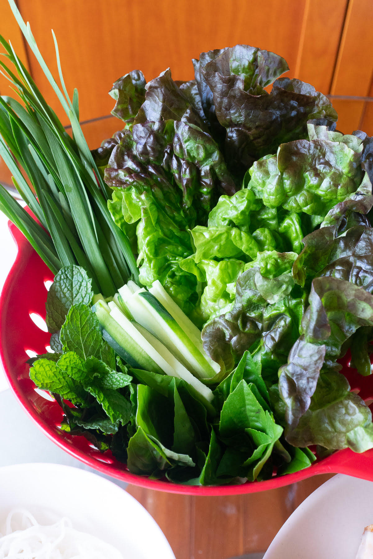 A colander filled with fresh vegetables and herbs used to make summer rolls.